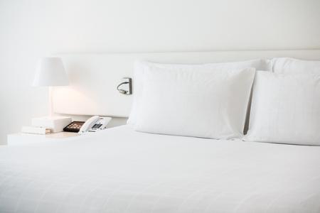 Oreiller blanc sur le lit avec décoration de lampe de table dans l'intérieur de la chambre Banque d'images