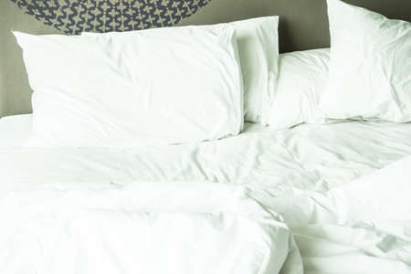 rumpled: Rumpled bed with white messy pillow decoration in bedroom interior