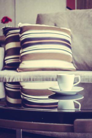 living wisdom: White coffee cup on table decoration in living room interior - Vintage Filter
