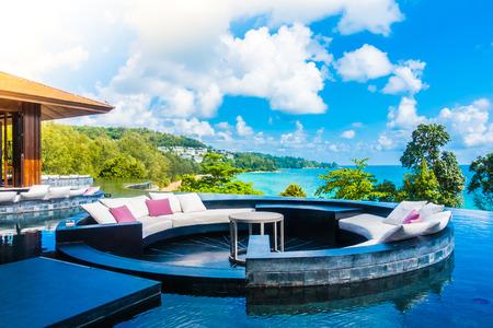바다와 바다를 볼 수있는 호텔 리조트의 소파 장식에 베개와 함께 아름다운 럭셔리 야외 파티오 스톡 콘텐츠 - 60548063