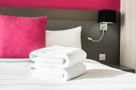 laundered: White towel on bed decoration in bedroom interior
