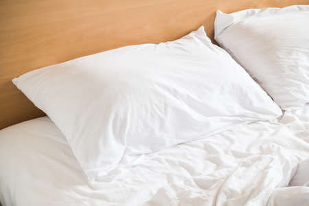 bed sheet: White messy pillow on sheet bed decoration in bedroom interior