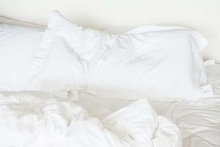 bed sheet: White sheet pillow on messy bed decoration in bedroom interior Stock Photo