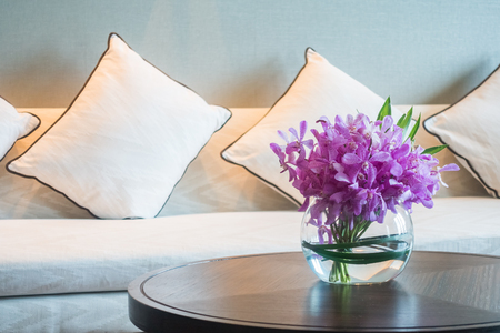 living room sofa: Vase flower decoration in living room with pillow and sofa Stock Photo