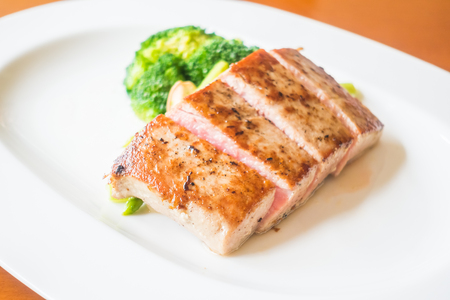 Selective focus point on tuna steak with vegetable in white plate