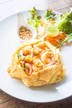 Pad thai noodles in white plate on wooden background