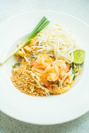 Fried noodles with shrimp on top in white plate - Pad Thai