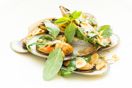 Fried mussel with white wine and basil leaf in white plate Stock Photo