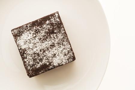 白い背景に分離された白いプレートにチョコレートのブラウニー