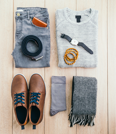 casual clothing: Beautiful men fashion with Sweater Jeans Belt Socks Wallet Watch and Brown leather shoes on wooden background - Vintage light filter Processing Stock Photo