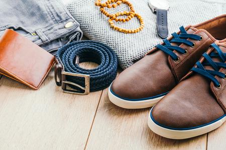 Mooie mannen mode met Sweater Jeans Belt Sokken Portemonnee Kijk en Bruin lederen schoenen op houten achtergrond - Uitstekende lichte filter Processing Stockfoto