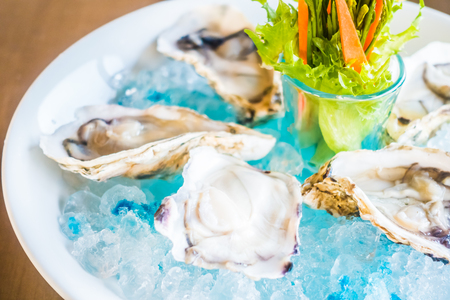 Raw and fresh Oysters in white plate with vegetable Stock Photo