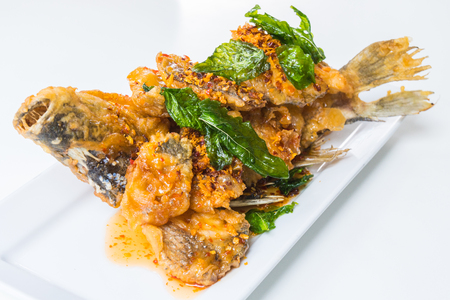 Fried fish with spicy sauce in white plate