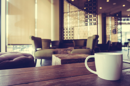 cofffee: White cofffee cup on wooden table in coffee shop cafe - Vintage Filter