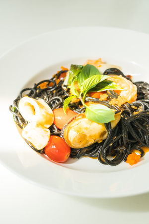 Black Spaghetti with seafood in white plate - Italian food style