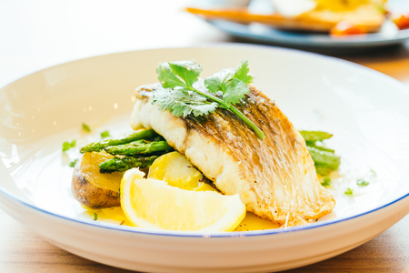 coalfish: Grilled Barramundi or pangasius fish and meat steak with vegetable and lemon in plate - Healthy food style