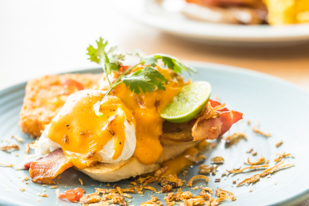 Egg benedict for breakfast in plate - Selective and soft focus point Stock Photo