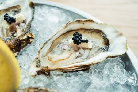 Raw and fresh Oyster with caviar on top and lemon on plate - Color Filter Processing Reklamní fotografie