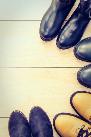 Leather boots and shoes on wooden background - Vintage Filter Stock Photo