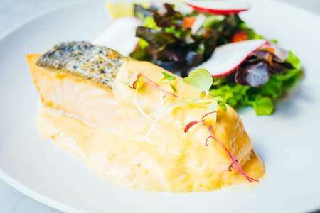 Grilled salmon fillet meat steak with vegetable in white plate - Color Filter Processing Stock Photo
