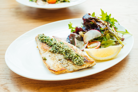 Grilled sea bass fish meat steak with vegetable and lemon in white plate - Color Filter Processing Stock Photo
