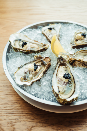Raw and fresh Oyster with caviar on top and lemon on plate - Color Filter Processing Stock Photo