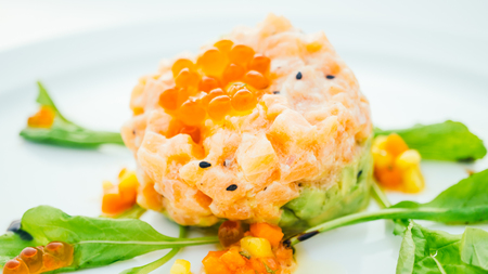 Raw fresh salmon tartare with avocado in white plate - Color Filter Processing Stock Photo - 82356148