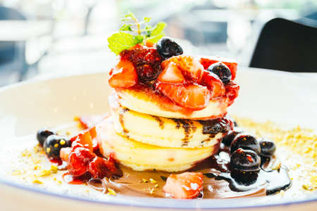 Sweet dessert Pancakes with mixed berry fruit in white plate Stock Photo
