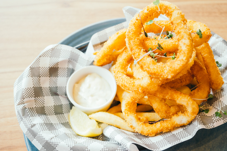 Deep fried calamari rings and french fries with sauce - Color Filter Processing Stock Photo - 82701129