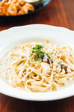 fettucine white cream sauce with shrimp and mushroom in white plate - Italian food style