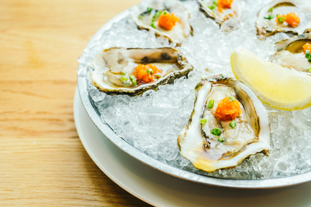 Raw and fresh oyster shell with lemon on ice Stock Photo