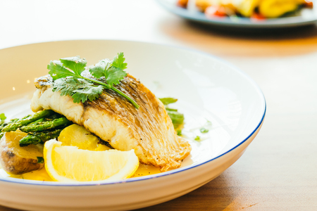 Grilled Barramundi or pangasius fish and meat steak with vegetable and lemon in plate - Healthy food style
