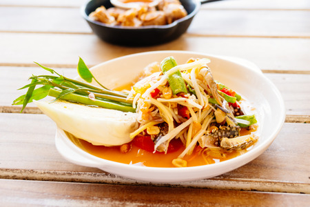 Spicy papaya salad or som tam with raw and fresh crab in white plate
