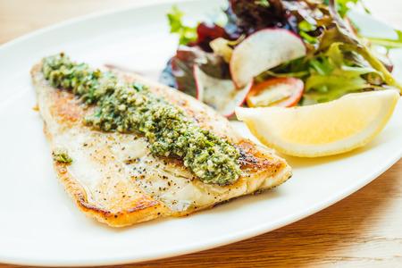 Gegrilde zeebaars vis vlees biefstuk met groente en citroen in witte plaat - Kleur filter verwerking Stockfoto