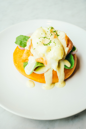 benedict: Donut bread with smoked salmon and egg benedict on top in white plate