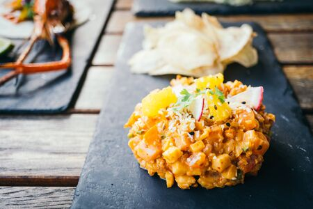 Raw fresh salmon meat tartare in black plate - Mexican food style , color filter Processing Stock Photo