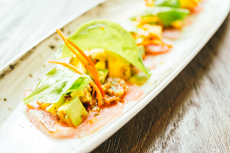Raw fresh tuna fish meat salad with avocado and mango on top in plate - Color Filter Processing Stock Photo
