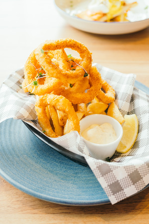 Deep fried calamari rings and french fries with sauce - Color Filter Processing Stock Photo