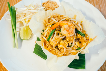 Pad thai noodles with shrimp or prawn on top in white plate