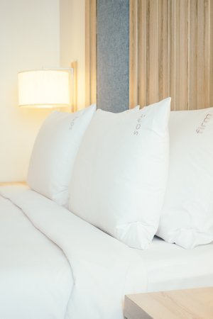 bedside: White pillow on bed with light lamp decoration interior of bedroom - Vintage soft filter