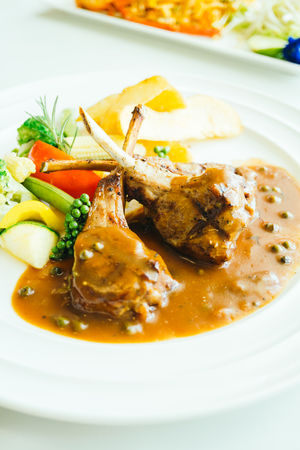 Grilled lamb chops meat with french fries and vegetable in white plate in white plate
