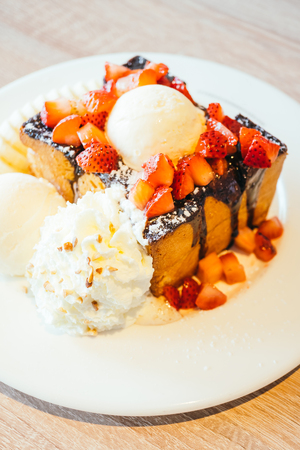 Sweet dessert Honey toast with ice cream and strawberry and banana in white plate