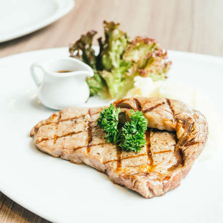 Grilled beef meat steak with sauce in white plate