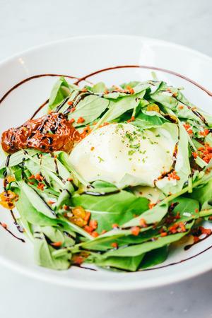 Eggs benedict with vegetable salad in white plate - Color Filter Processing Lizenzfreie Bilder