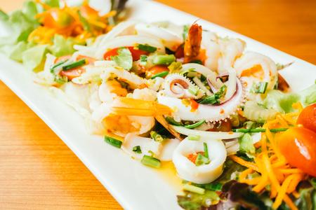 Mixed spicy seafood salad with thai food style in white plate Lizenzfreie Bilder