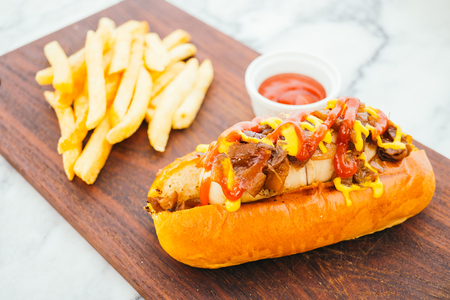 Hotdog with french fries and tomato sauce on wooden plate
