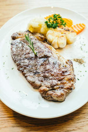 Grilled beef meat steak with vegetable in white plate