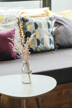 living room sofa: flower vase on table decoration with pillow and sofa interior - Vintage Filter Stock Photo