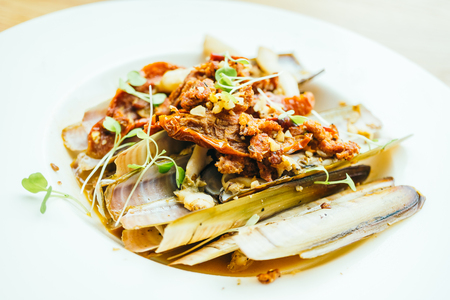 Fried spicy razor clams in white plate