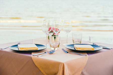 dining table and chairs: Romantic dining table setting with wine glass and other with sea and ocean background Stock Photo